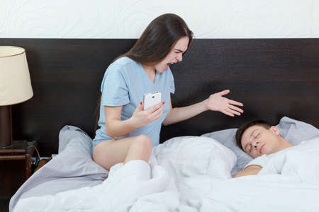 Young woman looking phone while man is sleeping soundly. Jealousy and suspicion in relationship. Caught cheating in messages and calls on mobile in bedroom. Problems in marriage, caucasian couple. Stock Photo