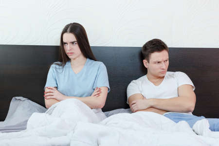 Portrait of unhappy and annoyed young caucasian couple after quarreling in bedroom under stress. Upset and angry man and woman sitting next to each other, relationship and marriage sex problems