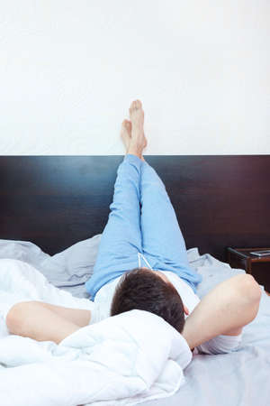 chillout: Young man resting, chillout or sleeping in bedroom in pajamas with his feet up on wall and body on bed. Lifestyle concept photo in domestic atmosphere
