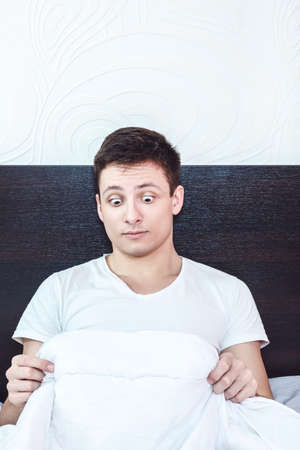 surprised and shocked good looking young man in bed looking down at his penis under white covers sheet in bedroom. Concept photo of male sexuality and man sex peny problems, domestic atmosphere.