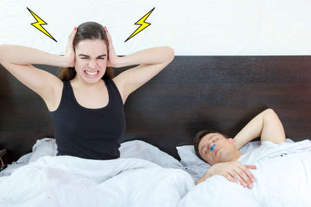 Young girl being angry on snoring boyfriend. Unhappy woman and her snoring husband.  Stock Photo