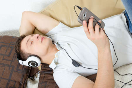 listening: Man fall asleep listening to music over smartphone with headphones , Handsome guy lying on sofa holding mobile phone and listening to music over headset Stock Photo