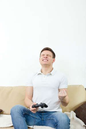 Emotional young man playing video games with joypad or joystick to console or pc. Guy at home in room sitting on bed with thrilled face expression, finally wins his opponent. Photo of winning in game. photo