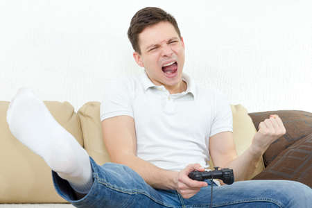 Emotional young man playing video games with joypad or joystick to console or pc. Guy at home in room sitting on bed with thrilled face expression, finally wins his opponent. Photo of winning in game.
