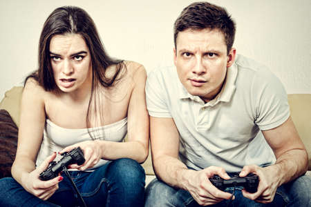Young couple sitting in living room and play video games on console or pc with joysticks while looking in screen or TV. Lifestyle photo of man and woman in jeans at home having fun or entertainment.
