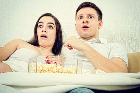 Frightened young attractive couple sitting on the couch in living room at home covered with blanket and watch scary horror on television with popcorn. Terrified man and woman watching violent movie