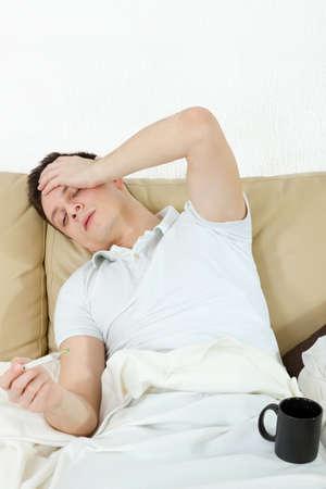 chory: Temperaturę Portret chorego w sypialni cierpiących na grypę pomiaru z termometrem i picia herbaty Zdjęcie Seryjne