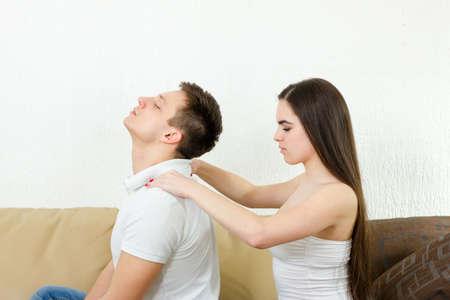 massieren: Junge Erwachsene Mann erhalten entspannende Massage von seiner jungen Frau gegeben, während sitzt auf dem Sofa im Wohnzimmer. Entspannung und Stressabbau nach dem harten Arbeitstag mit Massage zu Hause. Paare in der Widmung