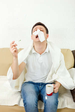 Young adult man suffering flu. Holding thermometer and tea in hand and has tissue paper on his nose, sneezing. Looking sad and desperate to temperature results. Sickness at home, recovery treatment.