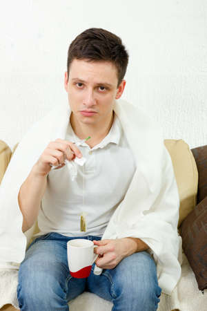 hayfever: Depressed young adult man wathcing at camera while holding thermometer and tea bag. Sickness at home, recovery treatment. Male covered with blanket indoor because fever and cold.