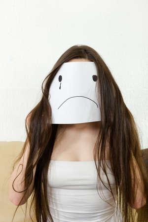 ojo humano: Mujer triste que se sienta en interiores. problemas de amor. crisis financiera con el dinero. Adultos ni�a se cubre la cara con una sonrisa dibujada en el papel con una l�grima. Infeliz persona joven adolescente con la cara sonriente decepcionados Foto de archivo