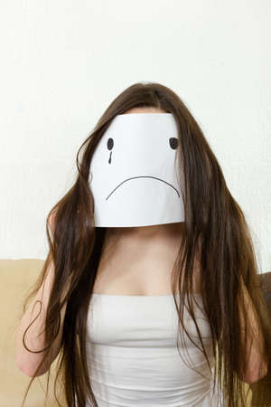people: Sad woman sitting indoor.  Love problems. Financial crisis with money. Adult girl cover her face with smile drawn on paper with one tear. Unhappy young teenager person  with disappointed smiley face