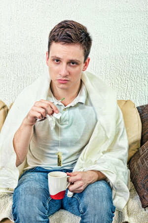 get tired: Young adult man treats himself with remedies. Get cold  and looking tired with eye bags and sitting on bed while holding thermometer and tea bag. Sickness at home, recovery treatment. Stock Photo