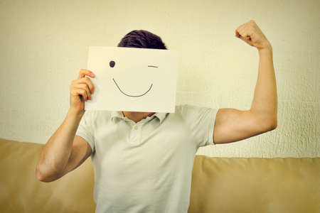 poor man: Boy winks and raises fist. Young male advertises successful model body. Man cover his face with happy smile drawn on paper.Fanny crazy  photo, man showing poor muscular biceps arm. Vintage retro style