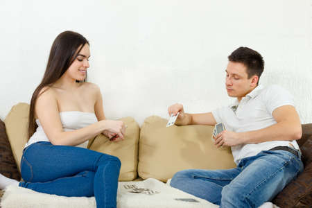 lucky man: Young adult couple perform foreplay. Two people playing card game on couch. Pretty girl i guy in jeans and white T-shirt siitng on sofa playing poker