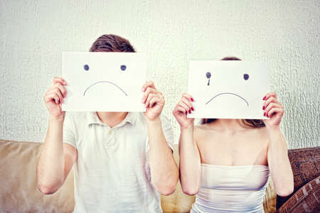 deplorable: Sad young couple. Unhappy young couple  in despair sitting on couch. Male and female with sad faces. Man and woman cover their faces with sad smile drawn on paper with one tear.