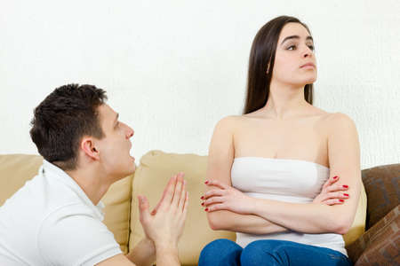 Crying male looking at female person. Portrait of couple, man and woman. Sad husband on his knees asking, begging for forgiveness wife who refuses to accept apology on sofa at home Stock Photo