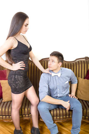 henpecked: Woman asks of man confidence and she is angry at him while man in bow tie looking her frightened. Henpecked. Handsome fashionable man with charming woman posing indoor. Trend couple. Lust and passion.
