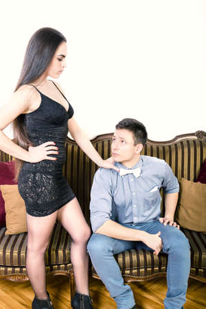 henpecked: Woman asks of man confidence and she is angry at him while man looking frightened by her. Henpecked. Portrait of handsome fashionable man with charming woman posing indoor. Young trend couple. Stock Photo