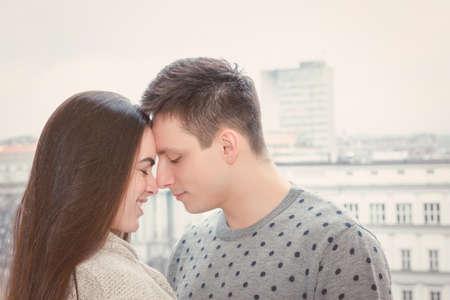 nariz: Pares en amor al tocar las narices al aire libre, chica t�mida e individuo junto con narices que sonr�e con vistas a la ciudad, el perfil de los pares cara a cara
