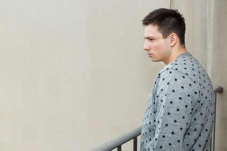 hombre solo: Hombre joven en el balcón de la depresión que sufren crisis emocional. Modelo masculino atractivo que mira hacia abajo desde el balcón. Persona en terraza da a la ciudad sombría y desolada después de la lluvia. Acosador ver a alguien