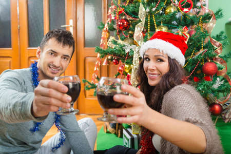christmas spending: Attractive couple enjoying Christmas time drinking wine celebrating ,  Two people spending New Year at home by Christmas tree with wine and gifts
