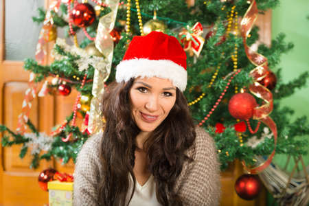 santa clause hat: Christmas woman in Santa Clause hat , Happy girl celebrating New Year at home by the Christmas tree smiling