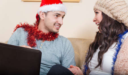 e shopping: Young Couple with Red Santa Hat, Sitting on Couch, Successful Shopping Concept with Laptop, Christmas E Shopping. People Using Credit Card to Internet Shop, Gift for Loved Ones