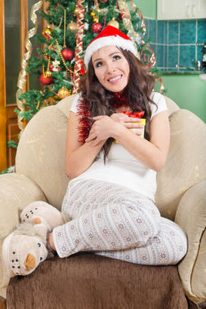 wearing slippers: Picture of Cheerful Santa Helper Girl with Gift Box Enjoying Holidays , Sweet Young Woman Sitting in Sofa at Home Wearing Fluffy Slippers and Holding New Year Present with Christmas Tree in Background
