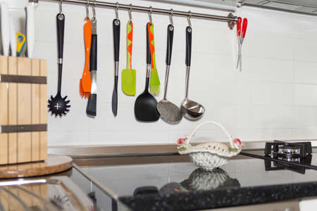 cuchillo de cocina: Interior de la pequeña cocina blanca. Brillante Fondo Moderno interior de la cocina. Debe tener Utensilios de cocina y electrodomésticos, cocina con una placa plana Negro, los accesorios necesarios. Cuchara, cuchara, cuchillo ...