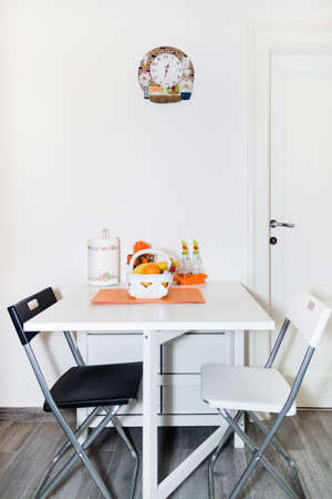 Interior of Small White Kitchen with Fresh Fruit Basket on the White Table With Two Chairs. Bright Modern Kitchen Interior Background.