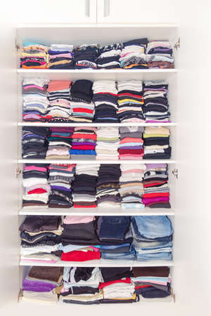 blouses: Dressing White Closet with Clothes Arranged Neatly Thickly Ordered. Colorful Wardrobe of Newborn, Kids, Toddlers, Young and Adults People. Full of All. Many T-Shirts, Pants, Shirts, Blouses, Shirt. Stock Photo