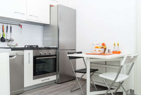 Interior of Small White Kitchen with Fresh Fruit Basket on White Table With Two Chairs. Bright Modern Kitchen Interior Background. Must Have Kitchenware and Appliances, Stainless Fridge, Stove, Sink. Banque d'images