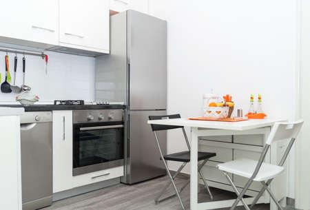 Interiér Malé bílé kuchyně s košíkem čerstvého ovoce na bílém stůl se dvěma židlemi. Světlé pozadí Moderní interiér kuchyně. Must Have kuchyňské a spotřebiče, nerezová lednice, sporák, dřez.