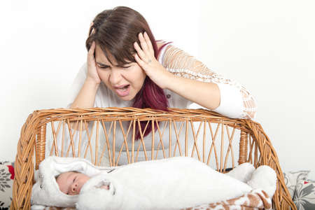 Woman with Face Expression Looking at Baby Cradle. Insufficient Sleep Because Baby Crying, Insomnia and Lack of Sleep Stock Photo