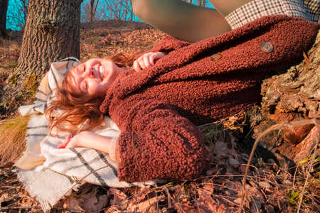 red-haired girl resting and enjoying the setting sun Standard-Bild