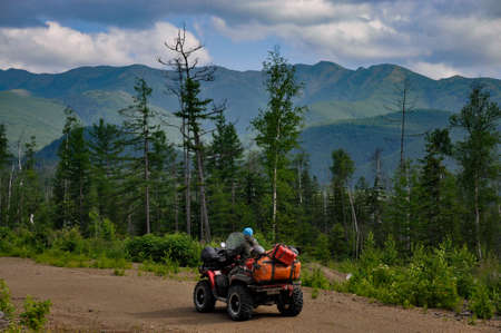 beautiful photo about traveling on an ATV in the forest and mountain area. you see the ATV riding the road with a forest and mountains on a background