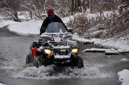 An ATV on wheels crosses a frozen river breaking ice