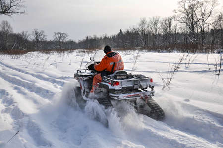ATV on tracks ride on a snowy road in the taiga