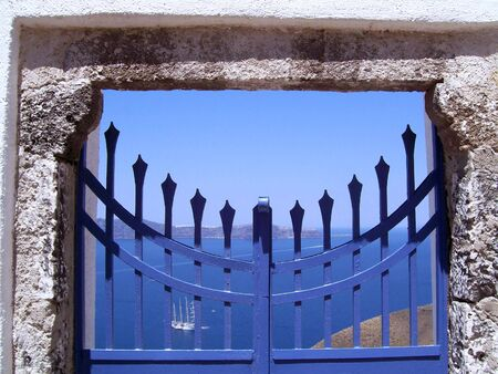 An image of a blue gate that appears to lead to a sheer drop down the mountain photo