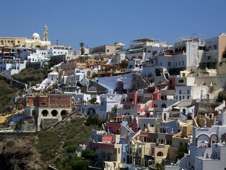 mountainside: image of Fira mountainside houses beautifully decorated with bright colours Stock Photo