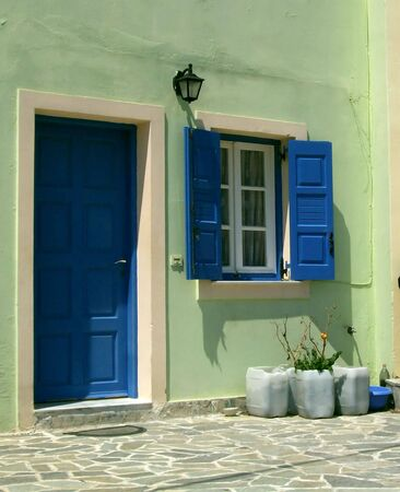 A traditional style greek house with the blue door and windowshutters photo