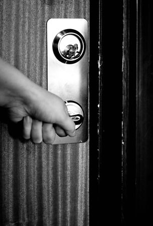door with key and hand holding handle Stock Photo