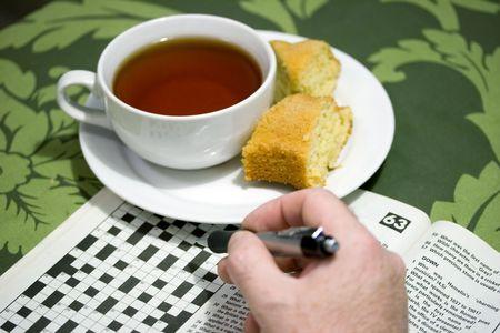 クロスワード パズルとお茶の朝のコップ 写真素材