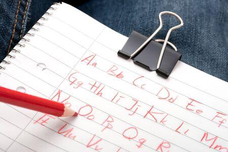 foglio a righe: scrivere l'alfabeto su carta governato con una matita rossa