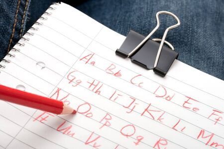ruled: writing the alphabet on ruled paper with a red pencil Stock Photo