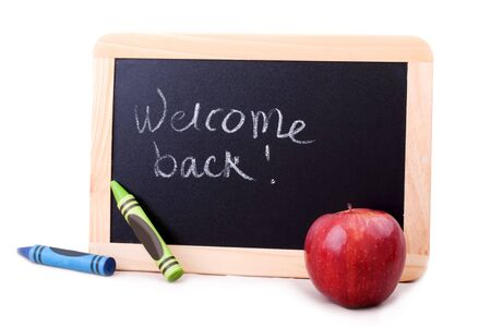 small blackboard with welcome back message, apple & crayons
