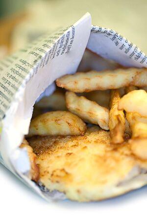 新聞に包まれた伝統的な魚 & チップ、