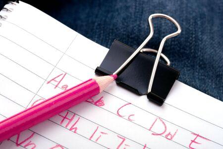 foglio a righe: scrivere l'alfabeto su carta governato con una matita di colore rosa