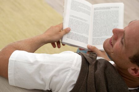 young man reading a good book and smiling Stock Photo